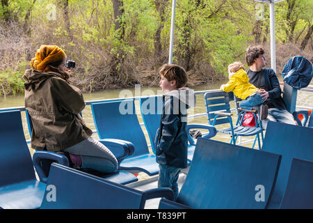 Nature Reserve Delta of the Danube River. Romania. April 20, 2019. A cruise ship swims along the river. Tourists on the deck of a cruise ship view and - Stock Image