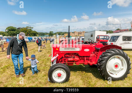 A father & son looking at tractors at the Holkham Country Fair in the grounds of Holkham Hall in North Norfolk. - Stock Image