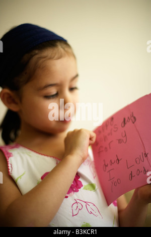 Five year old girl holds father's day card she made herself. 'Happy father's day for my dad I love yoo - Stock Image
