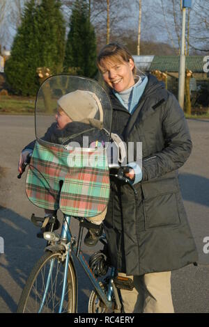 Front view happy over 30 caucasian mother and child in seat standing near bicycle outdoors and happy look at camera - Stock Image