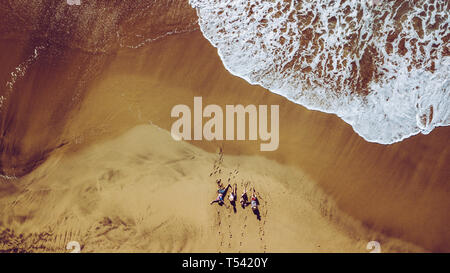 Group of friends people enjoying the beach laying on the sand - aerial top view with waves comnig, summer vacation travel lifestyle for young men and  - Stock Image