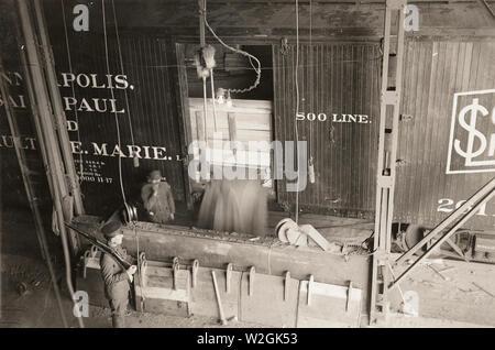 Pillsbury Flour Mills, Minneapolis, MN - Unloading wheat using power-operated shovels ca. 1916-1917 - Stock Image