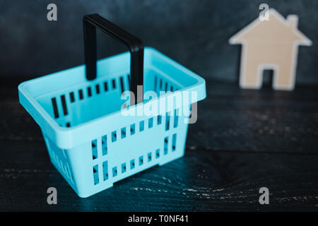 buying decor items or furniture concept: shopping basket and small cardboard house next to it - Stock Image
