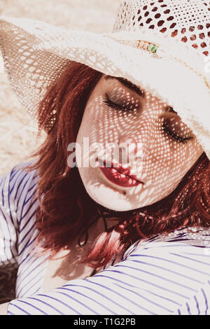 Redhead model protecting herself from sun with a hat in summer - Stock Image