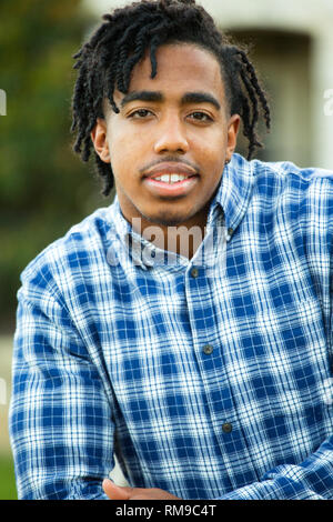 Handsome African American man smiling and standing outside. - Stock Image