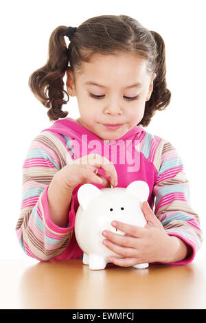 Stock image of little girl saving coin on her piggy bank over white background - Stock Image