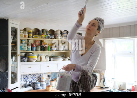 A middle-aged woman painting a ceiling in her kitchen. - Stock Image