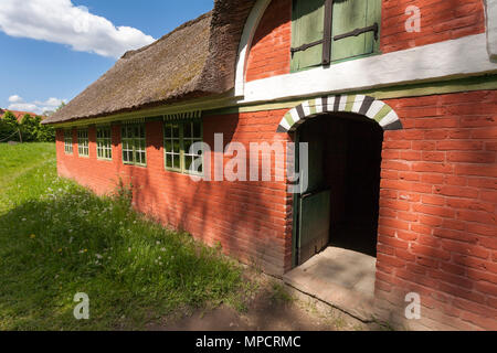 Red brick barn at the Folk Museum: A substantial red brick thatched barn stands in a lush grass meadow at the Lyngby Folk Museum. - Stock Image