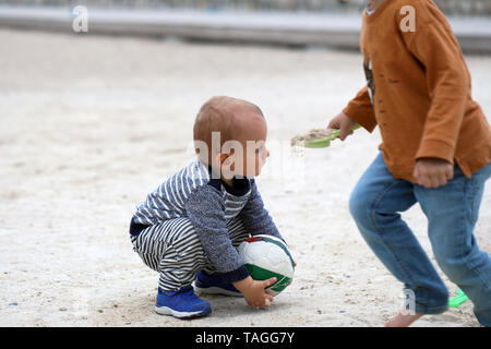 Adorable Blond Baby Boy is Playing With a Soccer Ball on Sand on Sea Beach - Stock Image
