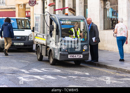 A Bath BID (business improvement district) ranger sat in a goupil electric utility vehicle talking to a man with a clip board - Stock Image