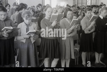 1950s, school assembly, pupils standing reading the bible, England, UK. - Stock Image