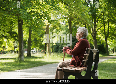 Senior woman sitting on park bench - Stock Image