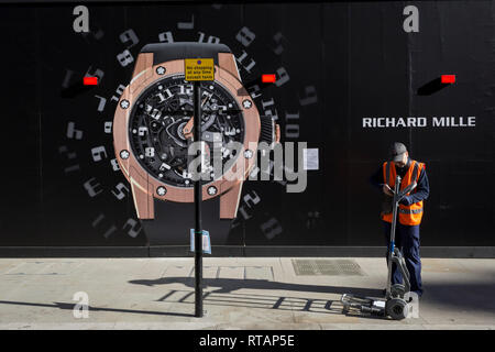 A courier checks his delivery device next to a construction hoarding of a watch outside the new Richard Mille shop in New Bond Street, on 25th February 2019, in London, England. - Stock Image