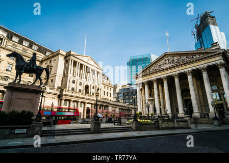 Red London bus trails outside the Bank of England, London, UK - Stock Image