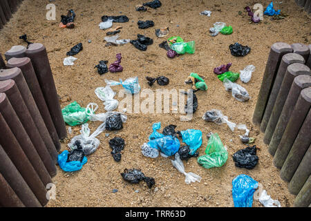 Fenced sandy public dog toilet area in city park filled with colourful discarded plastic dog poop bags - Stock Image