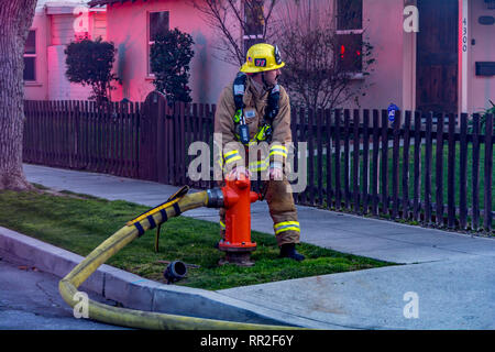 Burbank CA USA 23 February 2019 Burbank Firefighter turning on water from a hydrant at a house fire. Credit: Chester Brown/Alamy Live News - Stock Image
