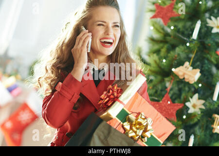 smiling young woman in red trench coat with shopping bag full of Christmas present boxes speaking on a cell phone near Christmas tree - Stock Image