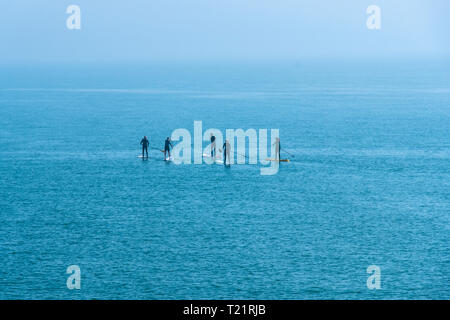 Hastings, East Sussex, UK. Paddle boarders put to sea across Hastings Old Town Harbour, on a flat calm sea, in the early morning mist - Stock Image