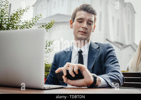 Close up of businessman sitting next to laptop, holding mobile phone in hand and looking at watches. - Stock Image
