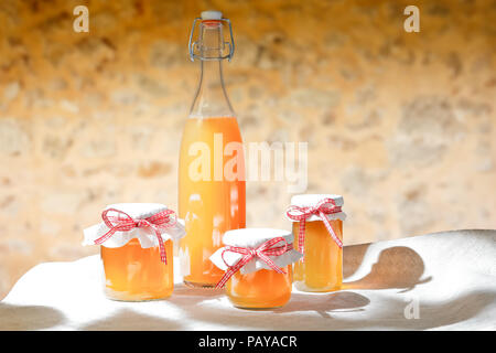Homemade fruit juice in a glass bottle and jelly in jars with linen cover and a nostalgic ribbon bow in bright sunshine in front of a rustic stone wall. - Stock Image