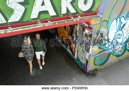A couple enter the graffiti covered St.James Barton roundabout subway complex (known as the Bear Pit), in Bristol, UK. - Stock Image