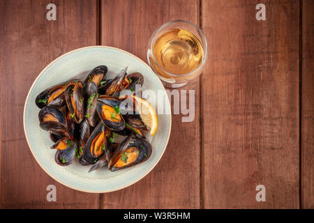 Marinara mussels, moules mariniere, with a glass of white wine, shot from the top on a dark rustic wooden background with a place for text - Stock Image
