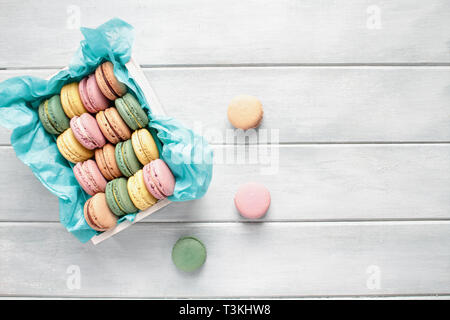 Assortment of fresh french macarons packaged in a pretty white wooden box with blue tissue on a white rustic table. Image shot from above with room fo - Stock Image