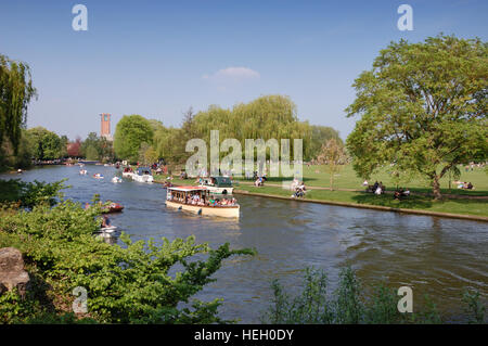 A river launch on the River Avon at Stratford-upon-Avon with the Royal Shakespeare Theatre and gardens in the background. - Stock Image