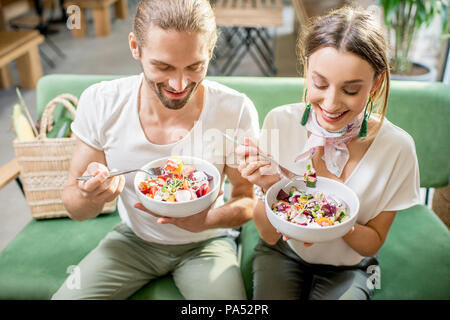Happy vegetarian couple eating healthy salad sitting together on the green sofa, close-up view from above - Stock Image