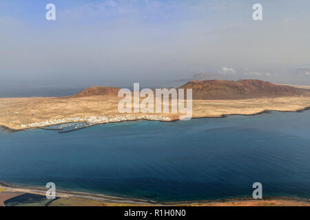 The small fishing and tourist village of Caleta del Sebo on the tiny island of La Graciosa next to Lanzarote Canary islands. Mount Bermeja is behind a - Stock Image