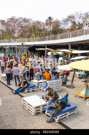 Young crowd dancing relaxing and dancing, at outdoor bar, Muelle uno, Malaga port, Andalusia, Spain. - Stock Image