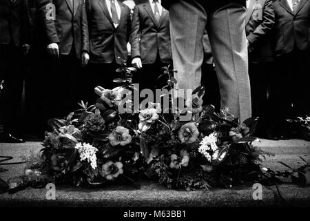 Male voice choir singing on stage at small eisteddfod in village hall Talsarnau Gwynedd Wales UK - Stock Image