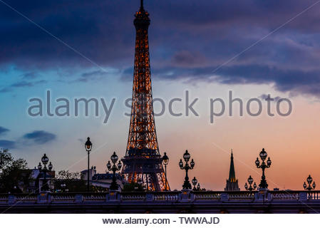 Art nouveau lamps on the Pont Alexandre III (bridge), with the Eiffel Tower behind, at twilight, Paris, France. The Pont Alexandre III is the most orn - Stock Image