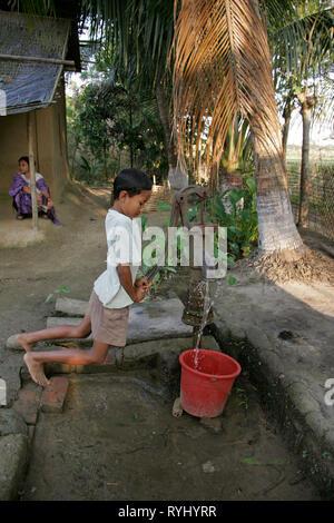 BANGLADESH Boy pumping weater from tube well, Garo tribal minority Haluaghat, Mymensingh region photo by Sean Sprague - Stock Image