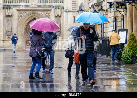 Bath, UK. 8th February, 2019. As storm Eric brings gales and heavy rain across the UK pedestrians are pictured outside Bath Abbey carrying umbrellas as they brave the heavy rain and wind. Credit: Lynchpics/Alamy Live News - Stock Image