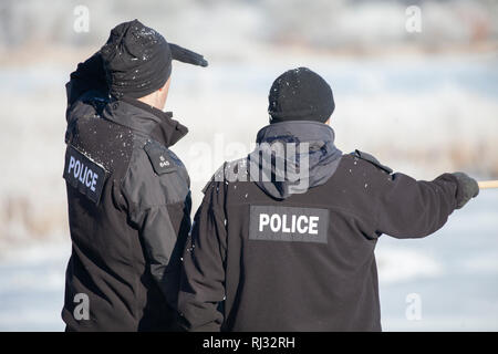 Police officers conducting a missing persons search checking the landscape around Lochwinnoch RSPB reserve, Renfrewshire, Scotland, UK - Stock Image