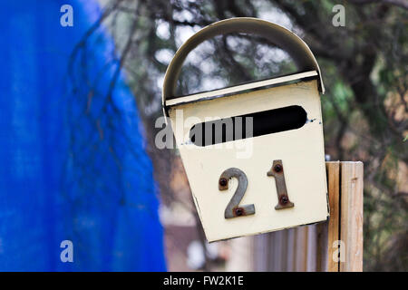 Old number 21 letter box tacked onto a fence. - Stock Image
