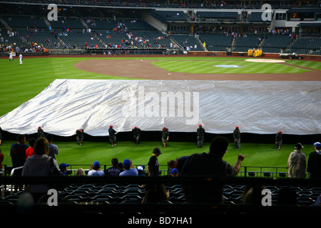 Citi Field grounds crew pulling the tarp off the field after a rain delay, Queens, NY, USA - Stock Image