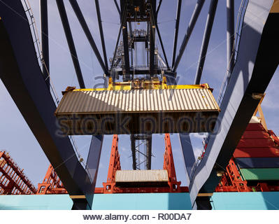 Crane unloading cargo container from ship - Stock Image