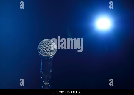 A microphone on stage in front of a spotlight - Stock Image