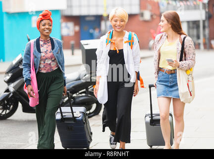 Smiling young women friends with suitcases walking on urban sidewalk - Stock Image