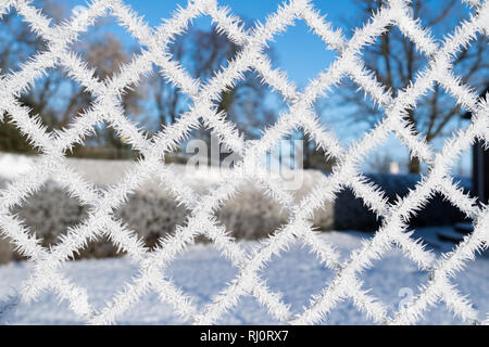 ice crystals on tennis court fencing - Stock Image