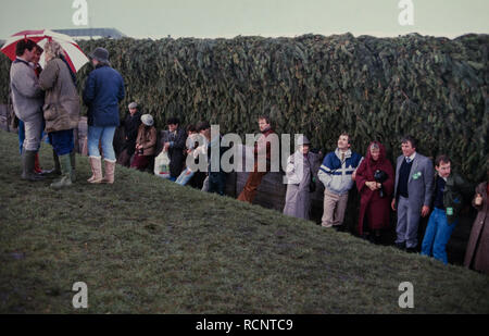 Grand National Horse race, Aintree, Liverpool, England UK. 1985 Spectators shelter from the rain in the lee of Bechers Brook fence. - Stock Image