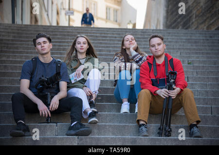Young traveling people sitting on the stairs. Men holding shooting equipment. Mid shot - Stock Image
