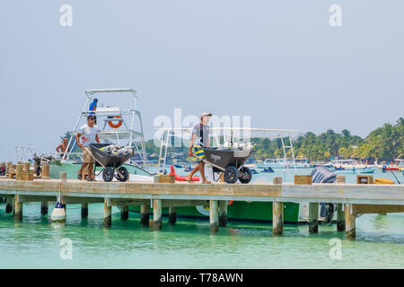 Workers remove depleted SCUBA tanks from a tourist dive boat at West Bay Beach in Roatan Honduras. - Stock Image
