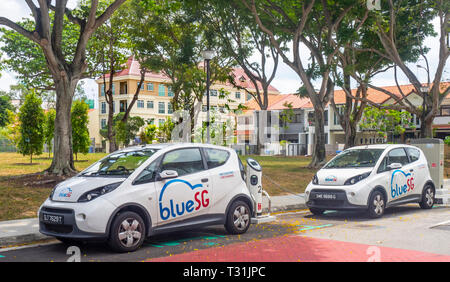 Blue SG Bolloré Bluecar, electric car charging at an electric vehicle recharching station in Singapore. - Stock Image