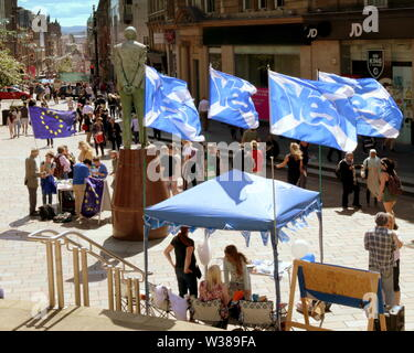 Glasgow, Scotland, UK. 13th July, 2019. Scottish Nationalist Remain information event took place under the statue of donald dewar, the founder of the Scottish parliament who turns his back on the yes for independance flags as he was a unionest.The stalls were positioned at the royal concert hall steps with the sunshine bathing the scenr shining uo the street. Credit: gerard ferry/Alamy Live News - Stock Image