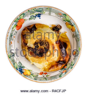 Baked apple pudding, cored then stuffed with sultanas. Whole apple oven baked dessert, UK. Cut out on a white background. - Stock Image