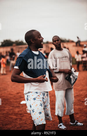 Mali, Africa - Young black man wearing a white t-shirt uniform while playing soccer with black african children, boys and caucasian volunteers in a ru - Stock Image