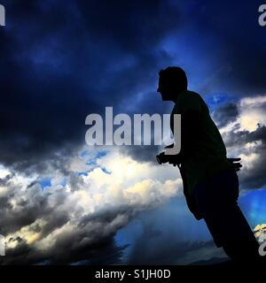 Silhouette of man with camera - Stock Image